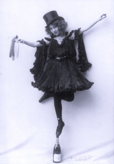 Model posed in ornate costumes: in black pressed pleats, with top hat; standing tip-toe on champagne bottle